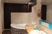 Une salle de bains avec douche et baignoire, avec vue sur jardin